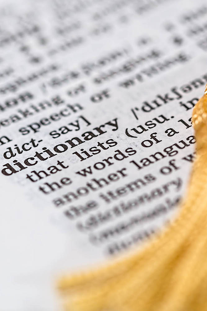An image of the definition of the word dictionary with a yellow tassel